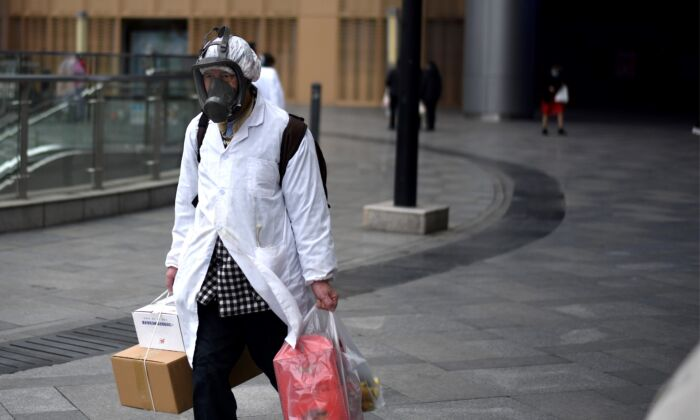 A man wearing a mask carries items he bought at a supermarket in Wuhan, China on March 30, 2020. (NOEL CELIS/AFP via Getty Images)