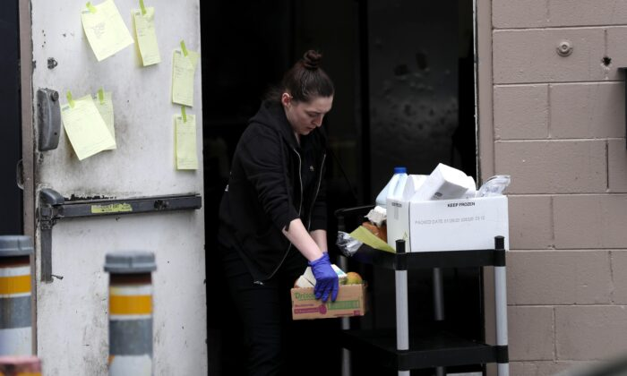 Maddy Dunn, a worker at Flights restaurant, fills orders during a drive thru no-touch groceries and to-go food service at the restaurant in Los Gatos, Calif., on March 23, 2020. (Justin Sullivan/Getty Images)