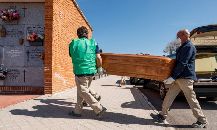 Mortuary employees wearing masks carry the coffin of a COVID-19 victim during a burial at the Fuencarral cemetery in Madrid on March 29, 2020. (Baldesca Samper/AFP via Getty Images)
