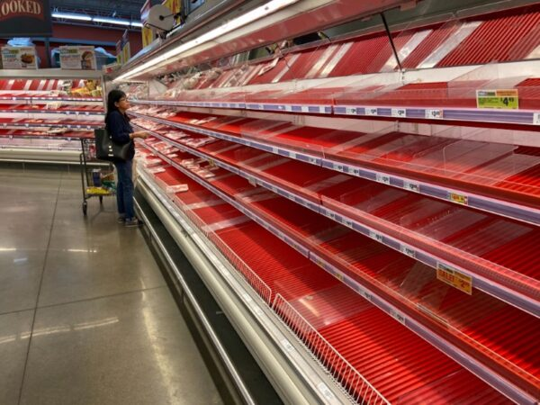 A shopper picks over the few items remaining in the meat section, as people stock up on supplies amid coronavirus fears