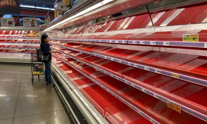 A shopper picks over the few items remaining in the meat section, as people stock up on supplies amid CCP virus fears, at a grocery store in Austin, Texas, on March 13, 2020. (Brad Brooks/File Photo/Reuters)