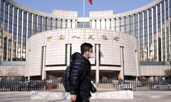 A man wearing a mask walks past the headquarters of the People's Bank of China, the central bank, in Beijing on Feb. 3, 2020. (Jason Lee/Reuters)
