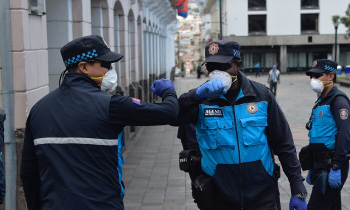 Policemen wearing face masks and gloves greet without using hands at Plaza Grande square in Quito, Ecuador, on March 19, 2020. (RODRIGO BUENDIA/AFP via Getty Images)
