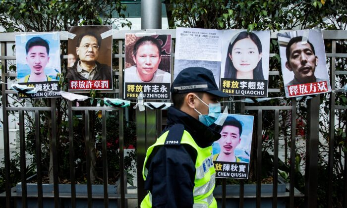 A police officer walks past placards of detained rights activists taped on the fence of the Chinese liaison office in Hong Kong on Feb. 19, 2020, in protest against Beijings detention of prominent anti-corruption activist Xu Zhiyong. Police in China have arrested Xu Zhiyong, a prominent anti-corruption activist who had been criticising President Xi Jinpings handling of the COVID-19 coronavirus. (Isaac Lawrence/AFP via Getty Images)