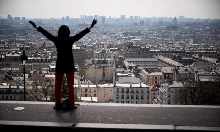 A woman stretches on top of the Montmartre hill neighbourhood of Paris on March 22, 2020, the sixth day of a strict nationwide confinement seeking to halt the spread of the CCP virus. (Lionel Bonaventure/AFP via Getty Images)