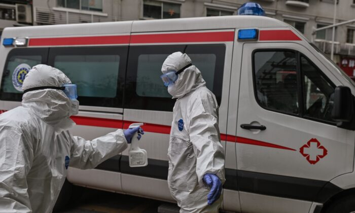 An ambulance medical staff sprays disinfectant on his colleague after they shipped a patient, who was cured from CCP Virus recently, at Wuhan Red Cross Hospital in Wuhan, China on March 30, 2020. (HECTOR RETAMAL/AFP via Getty Images)