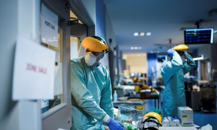 Medical workers put on their protective gears before working at the unit for CCP virus infected patients at the Erasme Hospital in Brussels, Belgium, on March 27, 2020. (Kenzo Tribouillard/AFP via Getty Images)