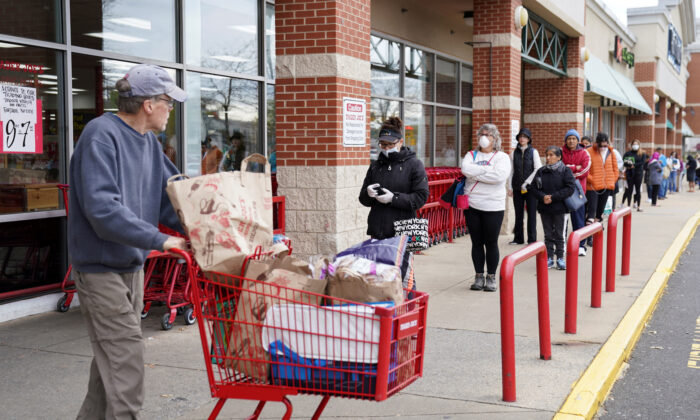 A shopper passes a self-distancing queue outside Trader Joe's, as they limited the amount of shoppers allowed in the store to help prevent the spread COVID-19, in Bailey's Crossroads, VA on March 31, 2020. (Kevin Lamarque/Reuters)