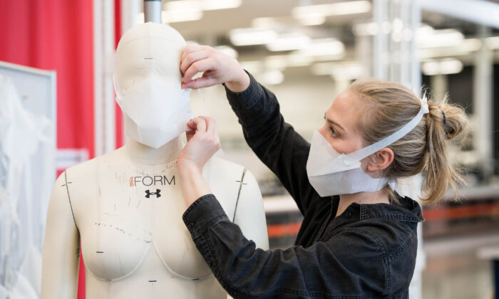 A member of staff at the Under Armour factory in Baltimore makes adjustments to a protective mask in this handout photograph from March 30 2020. (Under Armour)