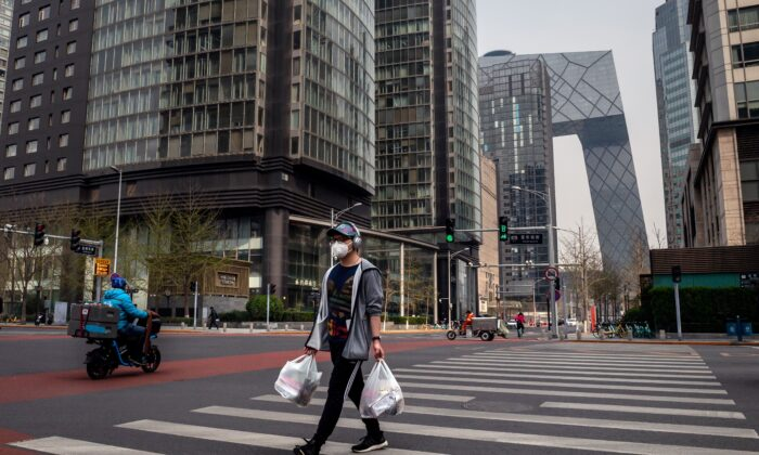 A man wearing a face mask amid the COVID-19 coronavirus outbreak crosses a street while carrying his groceries in Beijing, China, on March 30, 2020. (Nicolas Asfouri/AFP via Getty Images)
