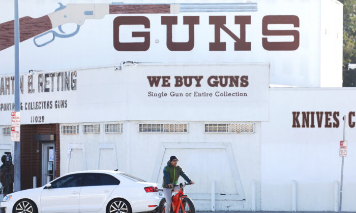 A cyclist rides past the Martin B. Retting gun store in Culver City, California, on March 24, 2020. (Mario Tama/Getty Images)
