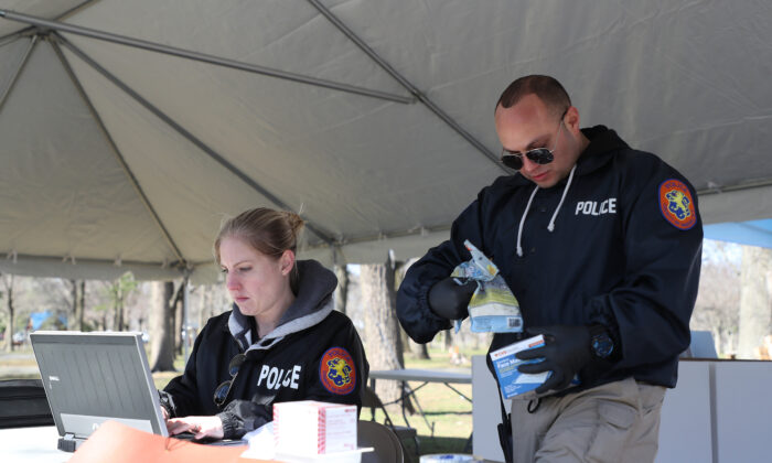 Nassau County police lead a donation drive to collect medical equipment such as N95 surgical masks, nitrile gloves, Tyvek suits, and antibacterial and disinfecting wipes to battle the CCP virus pandemic, at Eisenhower Park in East Meadow, New York, on March 24, 2020. (Al Bello/Getty Images)