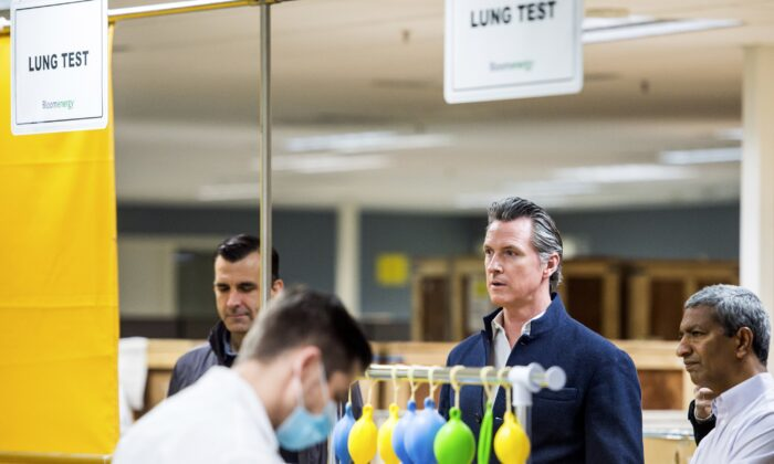 Gov. Gavin Newsom, second from right, is given a tour of the Bloom Energy campus in Sunnyvale, Calif., on March 28, 2020. (Beth LaBerge/KQED via AP, Pool)