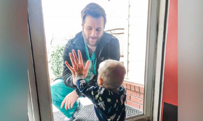Dr. Jared Burks sees his 1-year-old son crawl for the first time, as he touches a glass door from the outside while their son Zeke touches it from the inside of their Jonesboro, Ark. home in this photo posted on Facebook, on March 25, 2020. (Burks Family via AP)