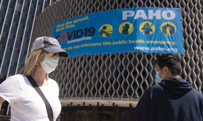People wear masks as they walk past a CCP virus awareness sign outside the World Health Organization in Washington on March 30, 2020. (Andrew Caballero-Reynolds/AFP via Getty Images)