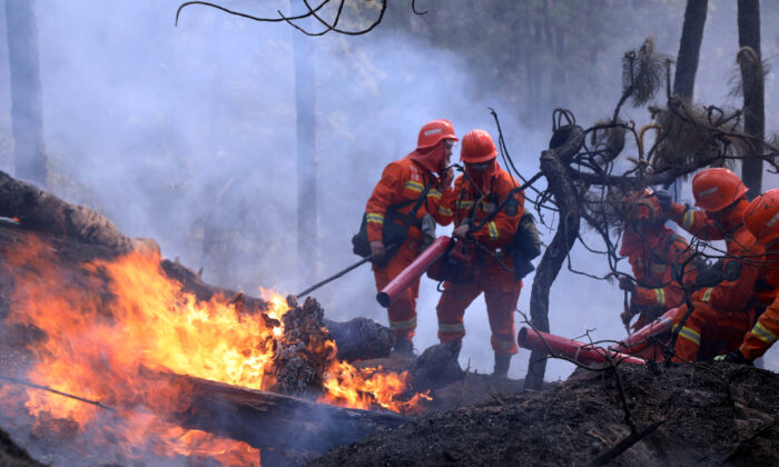 Firefighters work on extinguishing a forest fire that started near Xichang in Liangshan prefecture of Sichuan Province, China, on March 31, 2020. (China Daily via Reuters)