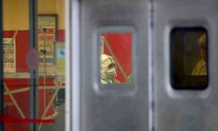 A healthcare worker is pictured through a window of the emergency room of the 12 de Octubre Hospital, amid the CCP virus outbreak in Madrid, Spain on March 31, 2020. (Sergio Perez/Reuters)