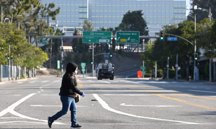 A woman wears a mask as she crosses an empty street near the Los Angeles Convention Center in downtown Los Angeles, California, on March 30, 2020. (Robyn Beck/AFP via Getty Images)