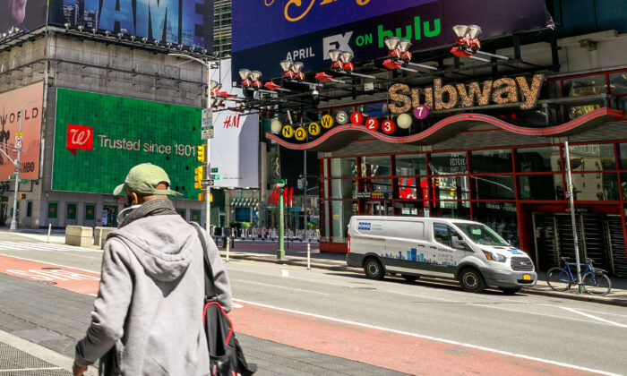 A man walks pass the nearly empty street outside Times Square subway station in New York on April 15, 2020. (Chung I Ho/The Epoch Times)