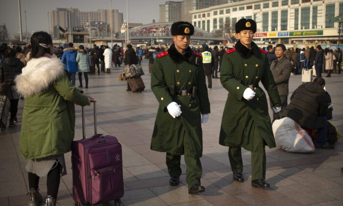 Chinese paramilitary police patrol outside the Beijing Railway Station in Beijing on Jan. 17, 2020. (Mark Schiefelbein/AP Photo)