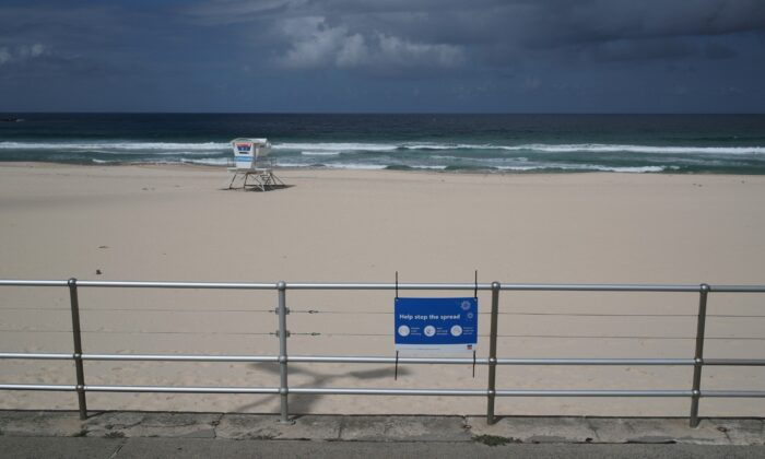 "A sign reading ""Help stop the spread"" is seen at an empty Bondi Beach, as the beach remains closed to prevent the spread of the coronavirus disease (COVID-19), in Sydney, Australia, on April 1, 2020. (Loren Elliott/Reuters)"