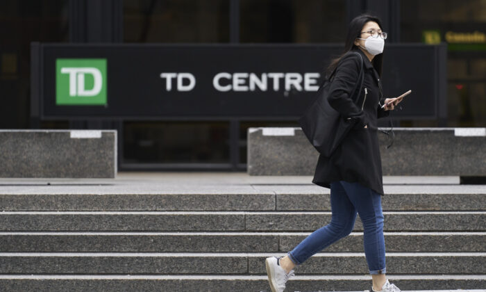 A woman in a mask walks in the financial district in Toronto, Ontario on March 24, 2020. (Geoff Robins/AFP via Getty Images)