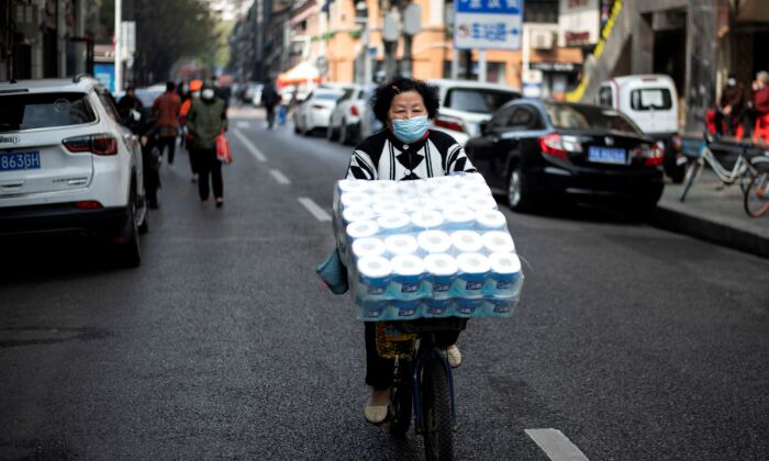 A woman is cycling along a street in Wuhan, China on April 1, 2020. (Photo by NOEL CELIS / AFP) (Photo by NOEL CELIS/AFP via Getty Images)