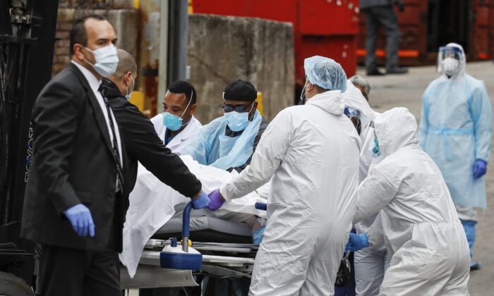 A body wrapped in plastic that was unloaded from a refrigerated truck is handled by medical workers wearing personal protective equipment due to CCP virus concerns at Brooklyn Hospital Center in New York on March 31, 2020. (John Minchillo/AP Photo)