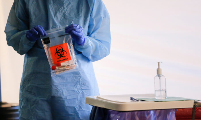 A nurse holds a completed test with patient samples at a drive-through testing site for the CCP virus in Washington state on March 9, 2020. (Lindsey Wasson/Reuters)