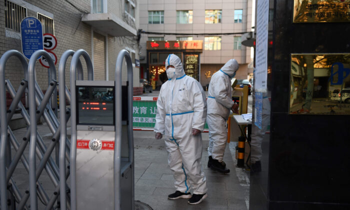 Security guards wear protective clothing as they wait at the entrance to a restaurant in Beijing on March 4, 2020. (Greg Baker/AFP via Getty Images)