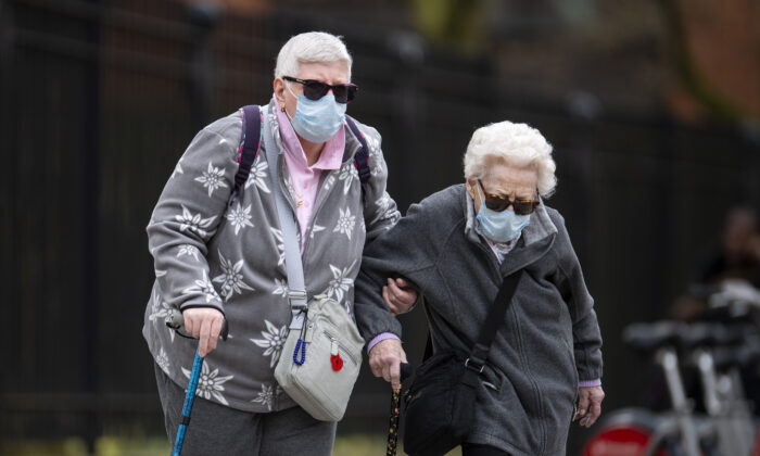 Elderly members of the public wearing masks walk down a street in central London on April 1, 2020. (Justin Setterfield/Getty Images)