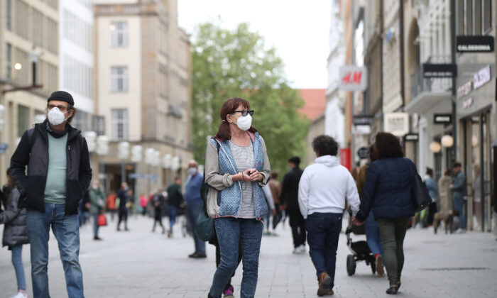 People wearing protective face masks walk on the main shopping street in Munich City during the coronavirus crisis on April 30, 2020 in Munich, Germany. (Alexander Hassenstein/Getty Images)