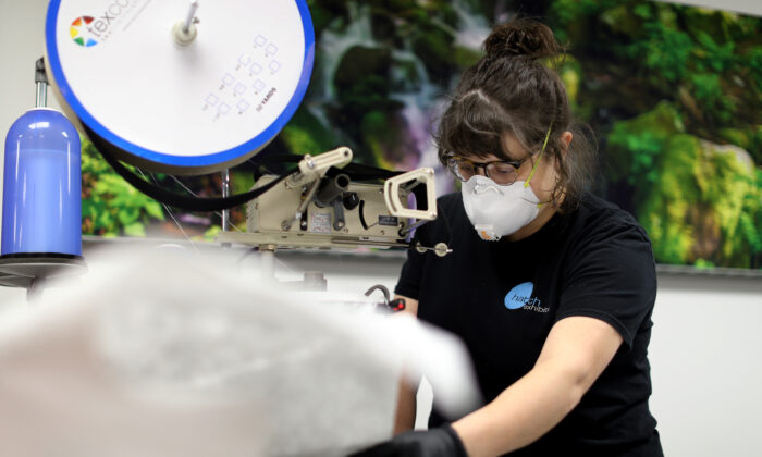 Hatch Exhibits fabricator and installer Morgan Frailey sews together medical gowns the company produces to protect people from the CCP virus, in Elkridge, Maryland, on March 31, 2020. (Chip Somodevilla/Getty Images)