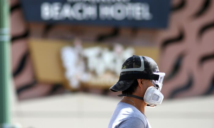 A man wears goggles and a mask as he walks a dog along Waikiki Beach in Honolulu on March 28, 2020. (Caleb Jones/AP Photo)