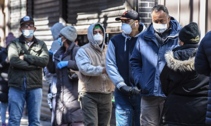 People stand in line while wearing face masks in the Elmhurst neighborhood in New York City on April 1, 2020. (Stephanie Keith/Getty Images)