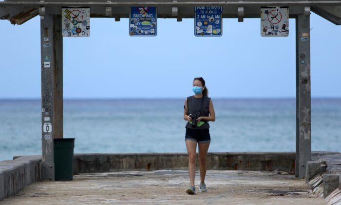 A woman wears a mask as she walks along a closed Waikiki Beach pier in Honolulu, Hawaii on March 28, 2020. (Caleb Jones/AP Photo)