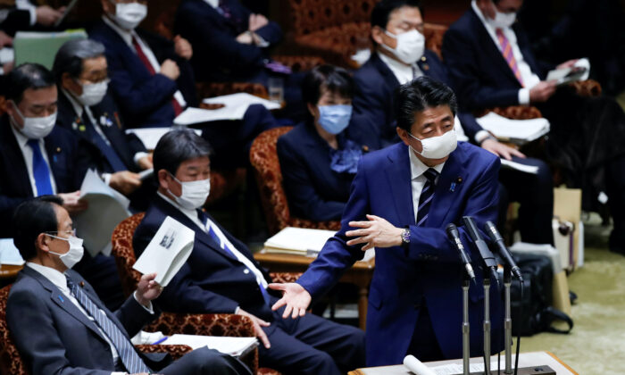 Japan's Prime Minister Shinzo Abe, wearing a protective face mask, gestures next to Japan's Finance Minister Taro Aso during an upper house parliamentary session in Tokyo, Japan on April 1, 2020. (Issei Kato/Reuters)