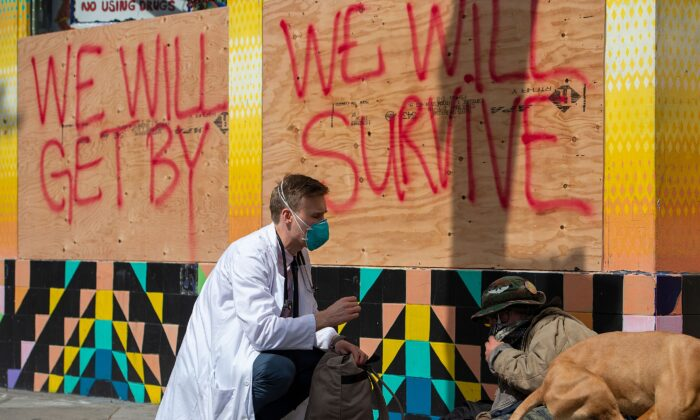 Stuart Malcolm, a doctor with the Haight Ashbury Free Clinic, speaks with homeless people about the coronavirus (COVID-19) in the Haight Ashbury area of San Francisco (Photo by JOSH EDELSON/AFP via Getty Images)