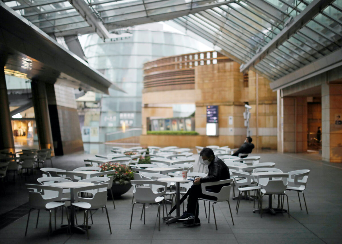 People wearing protective face masks, following an outbreak of the coronavirus disease (COVID-19), takes a rest next to almost empty seats of a cafe and restaurant at the Roppongi Hills complex in Tokyo