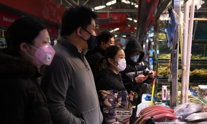 Local residents wear masks as they shop at a market in Beijing on Feb. 27, 2020. (Greg Baker/AFP via Getty Images)