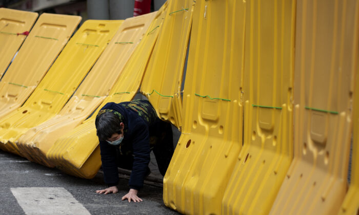 A elderly woman crawls under a yellow barricade separating a residential compound in Wuhan, China on April 2, 2020. (NOEL CELIS/AFP via Getty Images)