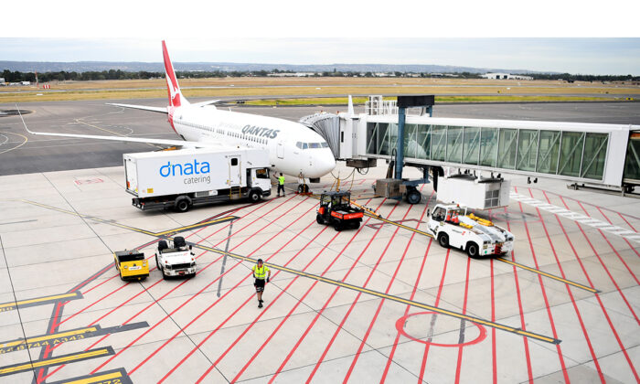Baggage handlers load a Qantas plane at Adelaide Airport, Australia on April 1, 2020. (Tracey Nearmy/Getty Images).