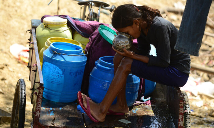 An Indian girl sits on a rickshaw trolley and drinks after collecting water in plastic barrels from a road side tap in Allahabad on March 22, 2016. (SANJAY KANOJIA/AFP via Getty Images)