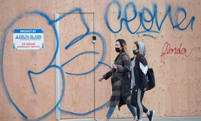 Two women wearing protective face masks make their way past a boarded up Banana Republic store in downtown Vancouver on March 30, 2020. (The Canadian Press/Jonathan Hayward)