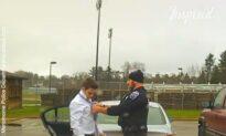 Police officer helps student tie a necktie