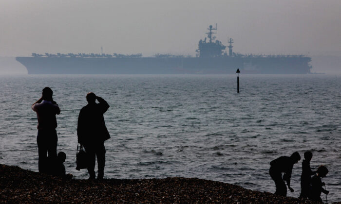 People stop to look at the USS Theodore Roosevelt anchored off Stokes Bay in Portsmouth, England, on April 6, 2009. (Matt Cardy/Getty Images)