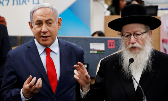 Israeli Prime Minister Benjamin Netanyahu and Health Minister Yaakov Litzman gesture as they deliver statements during a visit to the Health Ministry national hotline, in Kiryat Malachi, Israel, on March 1, 2020. (Reuters/Amir Cohen/File Photo)