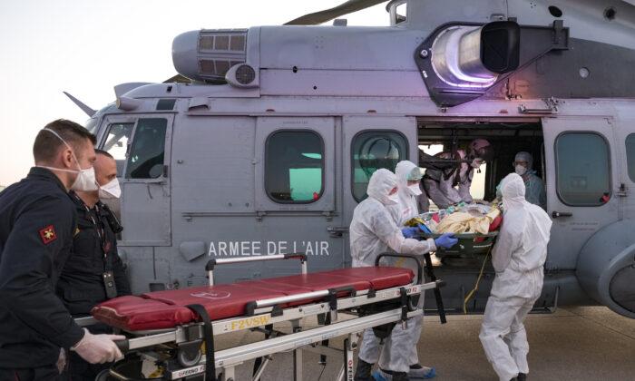Medics evacuate a COVID-19 patient at an airport near Paris, France, on April 1, 2020. (Julien Fechter/DICOD via AP)