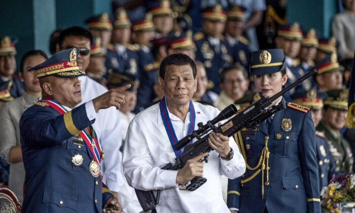 Philippine President Rodrigo Duterte holding a Galil sniper rifle with outgoing Philippine National Police (PNP) chief Ronald dela Rosa (L) during the change of command ceremony at Camp Crame in Manila on on April 19, 2018. (Noel Celis/AFP via Getty Images)