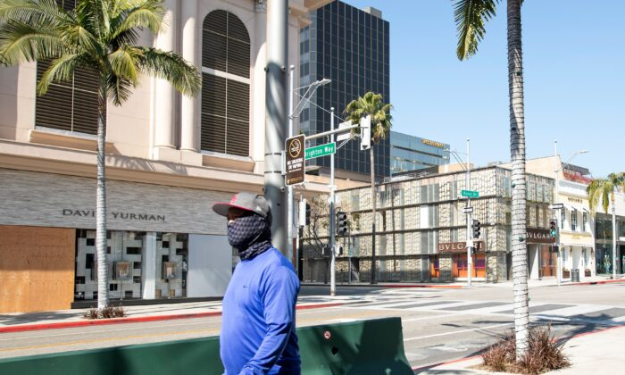 A person wearing a mask walks on Rodeo Drive in Beverly Hills, California, on April 1, 2020. (Valerie Macon/AFP via Getty Images)